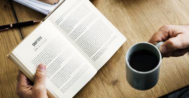 mannenhand met boek en koffie