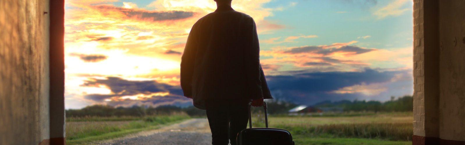 man op reis met koffer
