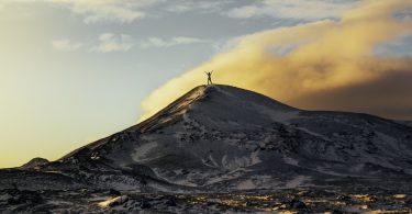 persoon op bergtop